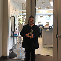 Deb Coffin in front of women's center, holding award