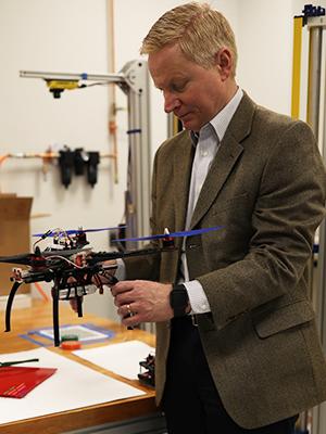 Dr. Kirk Kolenbrander holding a drone inside a CETA engineering lab