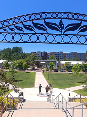 Stairs leading down to college campus greenspace with archway above