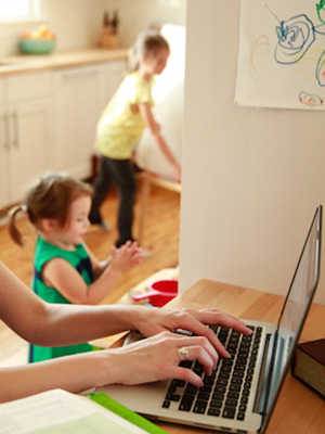 Woman types on laptop while two children play nearby