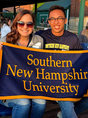 Woman and man smiling holding up banner that says Southern New Hampshire University